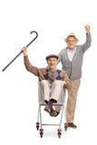 Χαρούμενο ηλικιωμένο άτομο που ωθεί ένα άλλο ηλικιωμένο άτομο σε ένα αυτοκίνητο αγορών Στοκ φωτογραφίες με δικαίωμα ελεύθερης χρήσης