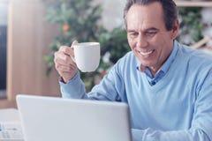 Χαρούμενο θετικό άτομο που απολαμβάνει τον καφέ του Στοκ φωτογραφία με δικαίωμα ελεύθερης χρήσης