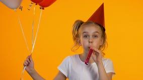 Χαρούμενο κορίτσι β-ημέρας με τα μπαλόνια χρησιμοποιώντας τον ανεμιστήρα κομμάτων και γελώντας στη κάμερα, διασκέδαση απόθεμα βίντεο