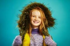 Χαρούμενο κορίτσι δέκα ετών στα χειμερινά ενδύματα πέρα από το μπλε υπόβαθρο Κοκκινομάλλες παιδί με τα όμορφα χαμόγελα φακίδων στοκ εικόνες