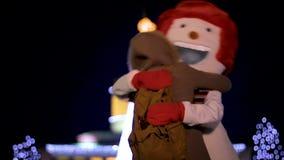 Χαρούμενο κορίτσι που αγκαλιάζει και που χορεύει με το χαριτωμένο χιονάνθρωπο Χριστουγέννων στα φω'τα διακοπών απόθεμα βίντεο