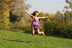 Χαρούμενο κορίτσι που πηδά στο λιβάδι Στοκ Εικόνα