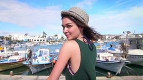 Χαρούμενο κορίτσι στην τοποθέτηση καπέλων στη κάμερα κατά τη διάρκεια των διακοπών στο υπόβαθρο αποβαθρών απόθεμα βίντεο