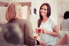 Χαρούμενο μακρυμάλλες brunette που εξετάζει το συνομιλητή της στοκ φωτογραφία