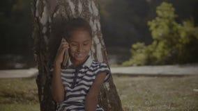 Χαρούμενο μικρό κορίτσι που μιλά στο κινητό τηλέφωνο κάτω από το δέντρο απόθεμα βίντεο