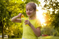 Χαρούμενο μικρό κορίτσι που στέκεται με τις φυσαλίδες σαπουνιών στα χέρια της κινηματογράφησης σε πρώτο πλάνο Στοκ εικόνες με δικαίωμα ελεύθερης χρήσης