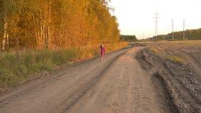 Χαρούμενο νέο κορίτσι που τρέχει και που πηδά από τη εθνική οδό κοντά στον τομέα Χρυσό βράδυ φθινοπώρου το φοβισμένο πορτρέτο κορ απόθεμα βίντεο