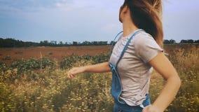 Χαρούμενο νέο κορίτσι που τρέχει στον τομέα, σε αργή κίνηση φιλμ μικρού μήκους