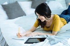 Χαρούμενο νέο brunette που παίρνει τις σημειώσεις στο κρεβάτι Στοκ Φωτογραφίες