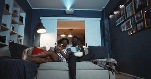 Χαρούμενο νεαρό περιστασιακό ζευγάρι από την Αφρική κάθεται στον καναπέ στο σπίτι και βλέπει ταινίες στον προβολέα με ποτά και πο φιλμ μικρού μήκους