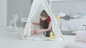 Χαρούμενο παιχνίδι μητέρων με το μωρό στην καλύβα των παιδιών απόθεμα βίντεο