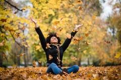 Χαρούμενο παιχνίδι εφήβων με τα ξηρά φύλλα σφενδάμου Στοκ Εικόνες