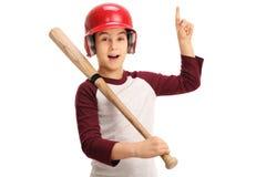 Χαρούμενο παιδί με τον εξοπλισμό μπέιζ-μπώλ που δείχνει επάνω Στοκ Φωτογραφία