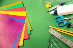 Χαρτικά για το σχολείο σε ένα πράσινο υπόβαθρο στοκ εικόνα