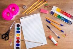 Χαρτικά σε έναν ξύλινο πίνακα Σημειωματάριο, στυλοί, μολύβια, χρώματα, ψαλίδι, συνδετήρες εγγράφου, γόμα, ξύστρα για μολύβια, κόλ στοκ εικόνες