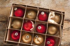 Χαρτοκιβώτιο χαρτονιού των κόκκινων και χρυσών σφαιρών Χριστουγέννων Στοκ Εικόνες