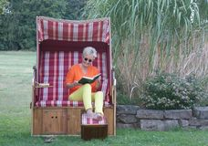 Χαρωπά με ένα γέλιο στο πρόσωπό της, η ξανθή γυναίκα διαβάζει στο χιουμοριστικό βιβλίο στοκ εικόνες