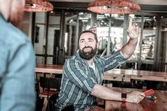 Χαρωπά χαμογελώντας φιλοξενούμενος μπαρ που καλεί το σερβιτόρο στοκ εικόνες