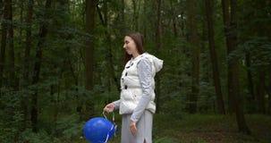 Χαρωπή γυναίκα που στέκεται και που ρίχνει ένα μπλε μπαλόνι σε ένα ξύλο την άνοιξη στην slo-Mo απόθεμα βίντεο