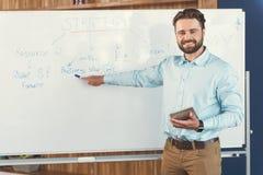 Χαρωπός νεανικός γενειοφόρος τύπος που λέει για τη στρατηγική εργασίας στην εργασία στοκ εικόνα