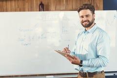 Χαρωπός νεανικός γενειοφόρος τύπος που γράφει κάτω τα σημαντικά στοιχεία στην εργασία στοκ φωτογραφίες
