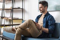 Χαρωπός νεανικός γενειοφόρος τύπος που ξοδεύει τον ελεύθερο χρόνο μέσα στο διαμέρισμα στοκ φωτογραφία με δικαίωμα ελεύθερης χρήσης