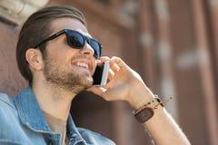 Χαρωπός νεαρός άνδρας που χρησιμοποιεί τη σύγχρονη συσκευή στην οδό στοκ φωτογραφία