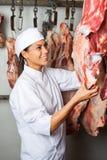 Χασάπης που ελέγχει την ποιότητα του κρέατος στοκ εικόνες