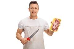 Χασάπης που κρατά ένα μαχαίρι και μια μπριζόλα στοκ φωτογραφίες