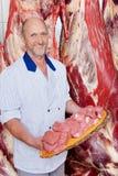 Χασάπης που κρατά ένα σύνολο δίσκων του τεμαχισμένου ακατέργαστου κρέατος στοκ φωτογραφία