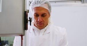 Χασάπης που κόβει το ακατέργαστο κρέας σε μια μηχανή πριονιών ζωνών απόθεμα βίντεο