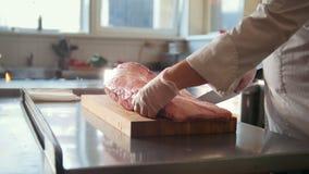 Χασάπης που κόβει το μεγάλο κομμάτι του φρέσκου ακατέργαστου κρέατος που βρίσκεται σε έναν ξύλινο πίνακα σε μια εμπορική κουζίνα απόθεμα βίντεο