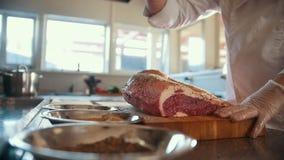 Χασάπης που προσθέτει τα καρυκεύματα στο μεγάλο κομμάτι του φρέσκου ακατέργαστου κρέατος που βρίσκεται σε έναν ξύλινο πίνακα σε μ απόθεμα βίντεο