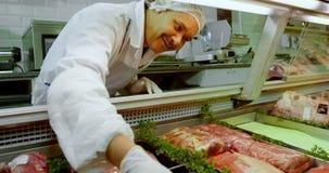 Χασάπης που τακτοποιεί το κρέας στο ψυγείο στο κατάστημα 4k απόθεμα βίντεο