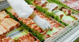 Χασάπης που τακτοποιεί το κρέας στο ψυγείο 4k απόθεμα βίντεο