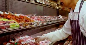 Χασάπης που τακτοποιεί το τυλιγμένο κρέας στο ράφι 4k απόθεμα βίντεο