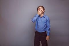 Χασμουρητά αγοριών εφήβων στο γκρίζο υπόβαθρο Στοκ φωτογραφίες με δικαίωμα ελεύθερης χρήσης