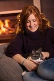 Χαϊδεύοντας γάτα έφηβη στο σπίτι Στοκ Εικόνες