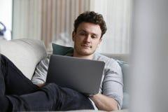 Χαλάρωση ατόμων στον καναπέ που χρησιμοποιεί το φορητό προσωπικό υπολογιστή Στοκ Φωτογραφία