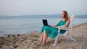 Χαλάρωση γυναικών στην παραλία με το lap-top της που μιλά skype απόθεμα βίντεο