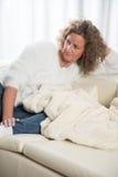Χαλάρωση γυναικών στον καναπέ Στοκ εικόνα με δικαίωμα ελεύθερης χρήσης