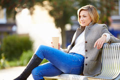 Χαλάρωση γυναικών στον πάγκο πάρκων με το take-$l*away καφέ Στοκ φωτογραφία με δικαίωμα ελεύθερης χρήσης