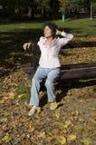 Χαλάρωση γυναικών στον πάγκο το φθινόπωρο Στοκ φωτογραφία με δικαίωμα ελεύθερης χρήσης