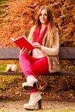 Χαλάρωση γυναικών στο φθινοπωρινό βιβλίο ανάγνωσης πάρκων Στοκ Φωτογραφία