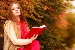 Χαλάρωση γυναικών στο φθινοπωρινό βιβλίο ανάγνωσης πάρκων Στοκ φωτογραφίες με δικαίωμα ελεύθερης χρήσης