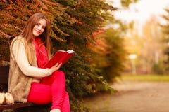 Χαλάρωση γυναικών στο φθινοπωρινό βιβλίο ανάγνωσης πάρκων Στοκ Εικόνες
