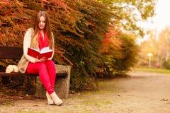 Χαλάρωση γυναικών στο φθινοπωρινό βιβλίο ανάγνωσης πάρκων Στοκ Εικόνα