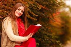 Χαλάρωση γυναικών στο φθινοπωρινό βιβλίο ανάγνωσης πάρκων Στοκ εικόνες με δικαίωμα ελεύθερης χρήσης