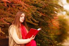 Χαλάρωση γυναικών στο φθινοπωρινό βιβλίο ανάγνωσης πάρκων Στοκ Φωτογραφίες