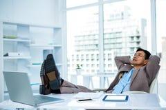 Χαλάρωση επιχειρηματιών με τα πόδια του στο γραφείο του Στοκ φωτογραφία με δικαίωμα ελεύθερης χρήσης